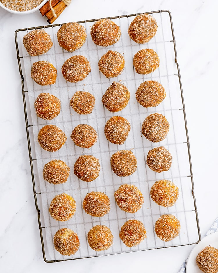 A cooling rack full of cinnamon sugar soft pretzel balls laid out in rows.