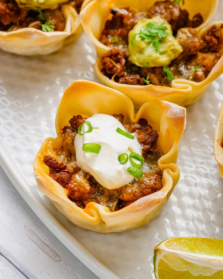 Wonton taco cups on a white plate. The wonton wrapper looks like a clover going up the sides with petals, and it is filled with ground beef, and topped with sour cream, and green onion slices.