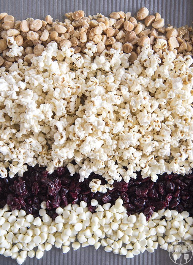 White Chocolate Cranberry and Macadamia Popcorn Mix - This simple snack mix is full of white chocolate chips, dried cranberries, chopped macadamia nuts and salty popcorn for a quick snack!