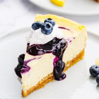 A slice of blueberry cheesecake on a white plate topped with blueberry sauce, whipped cream, and fresh blueberries.