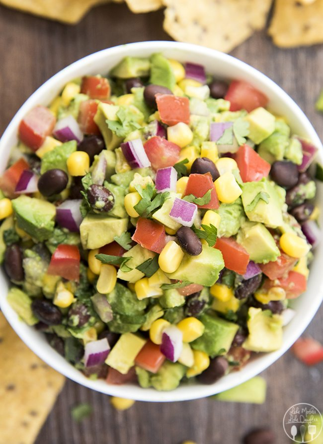 Corn and Black Bean Guacamole - This guacamole is stuffed full of corn, black bean, diced tomatoes and onions for a delicious flavorful guacamole. Perfect served with chips or on top of your favorite mexican dishes!