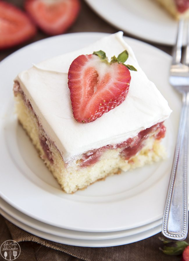 A slice of cake on a plate, with pokes full of strawberry sauce and topped with whipped cream and a slice of a strawberry.