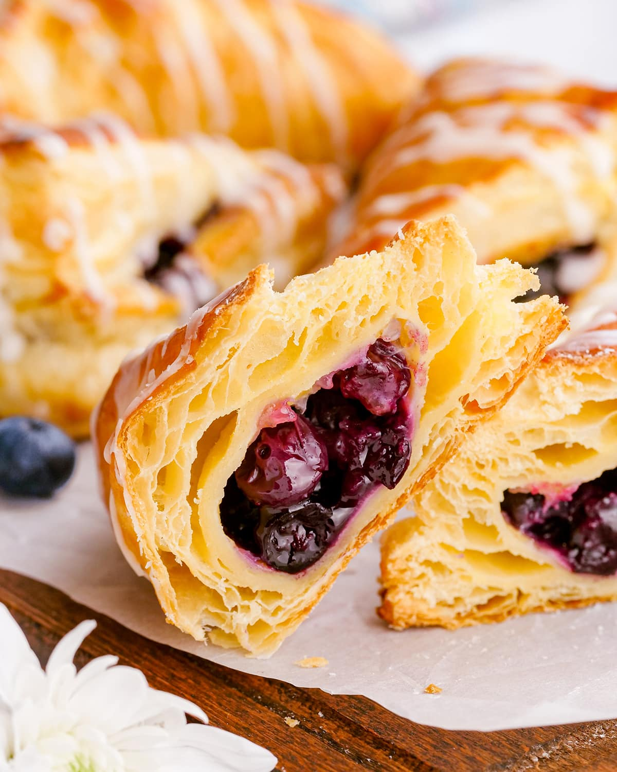 A blueberry turnover cut in half to show the flaky layers, and the blueberry filling.