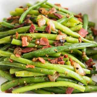 A white baking dish full of green beans covered in bacon pieces and sautéed onion.