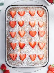 A strawberry yogurt cake topped with powdered sugar and sliced strawberries