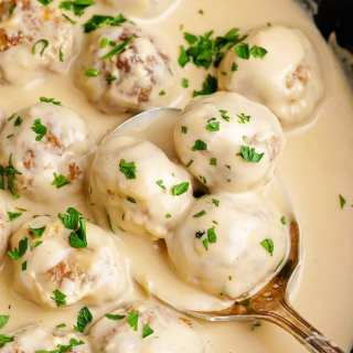 Swedish meatballs in a pot, in a creamy white gravy sauce, and sprinkled with fresh parsley.