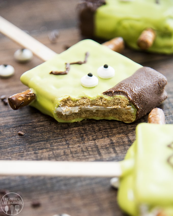 Frankenstein pops are smores on a stick made green and decorated to look like Frankenstein's monster and are perfect for Halloween