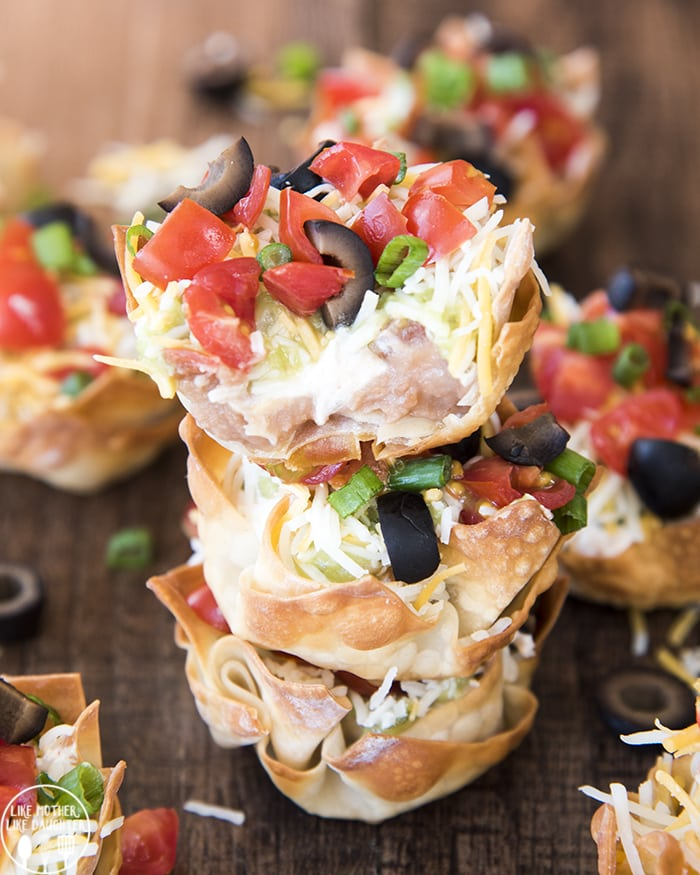 Wonton cups filled with refried beans, sour cream cheese, diced tomatoes, green onion, and olives. There are three of these cups stacked, the top is split open revealing the insides.