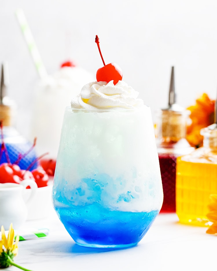 A blue colored Italian cream soda topped with whipped cream and a maraschino cherry.