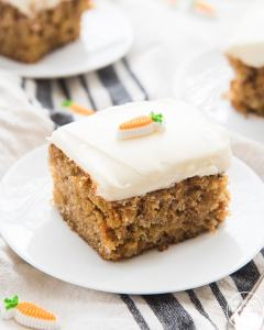 A slice of carrot cake on a small white plate. It's a square slice with a thick layer of cream cheese frosting, and topped with a candy carrot on top.