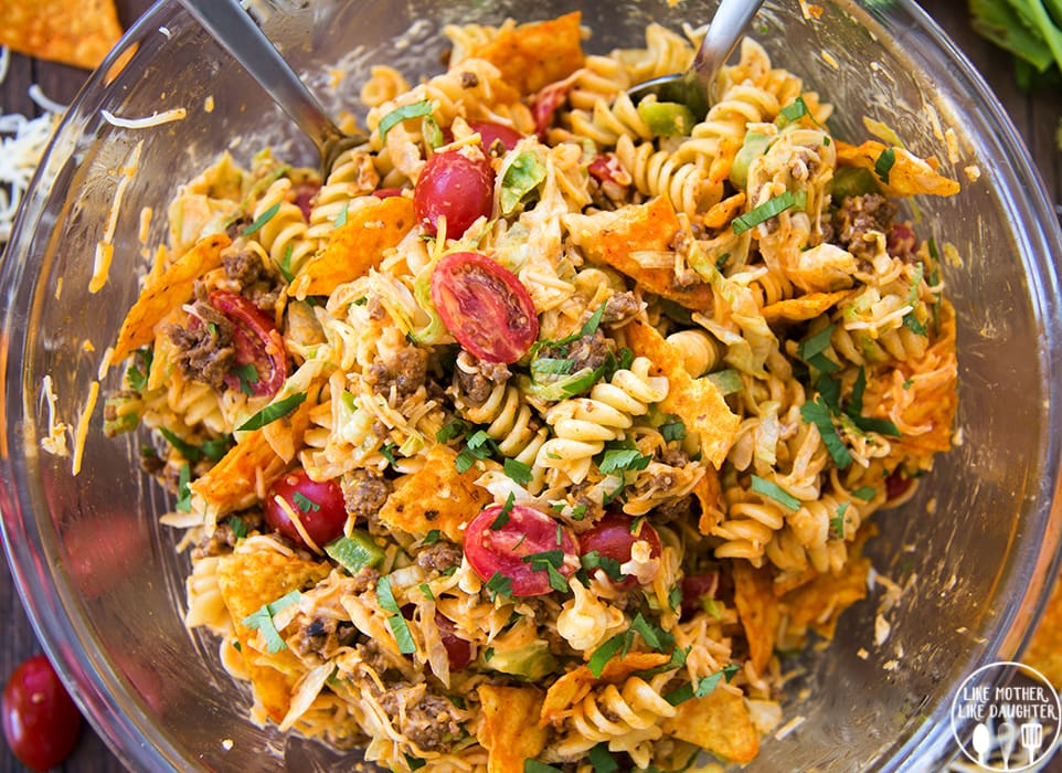 An overhead shot of a glass bowl full of a taco pasta salad, with rotini pasta, Doritos, tomatoes, ground beef, and topped with cilantro.