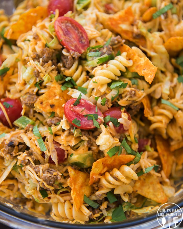 A close up of a glass bowl full of a taco pasta salad, with rotini pasta, Doritos, tomatoes, ground beef, and topped with cilantro.
