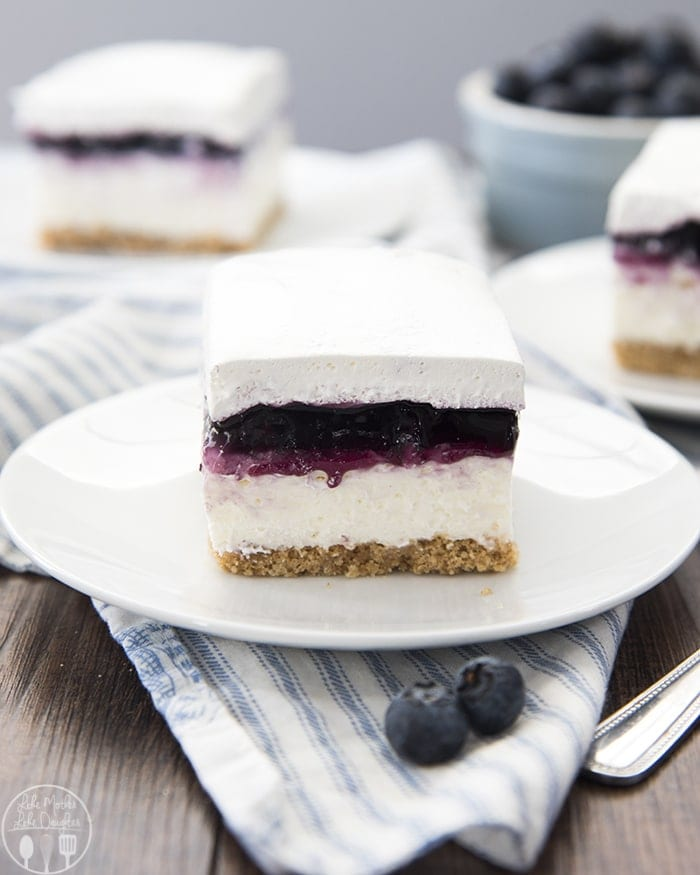These no bake blueberry cheesecake bars are a perfect easy dessert. With a buttery graham cracker crust, creamy cheesecake layer, blueberry pie topping, and cool whipped cream to top it off!