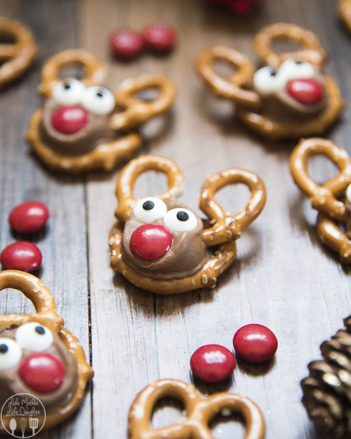 A pretzel topped with a melted rolo, that is topped with two candy eyes, a red m&m, and two pretzels to look like a reindeer.