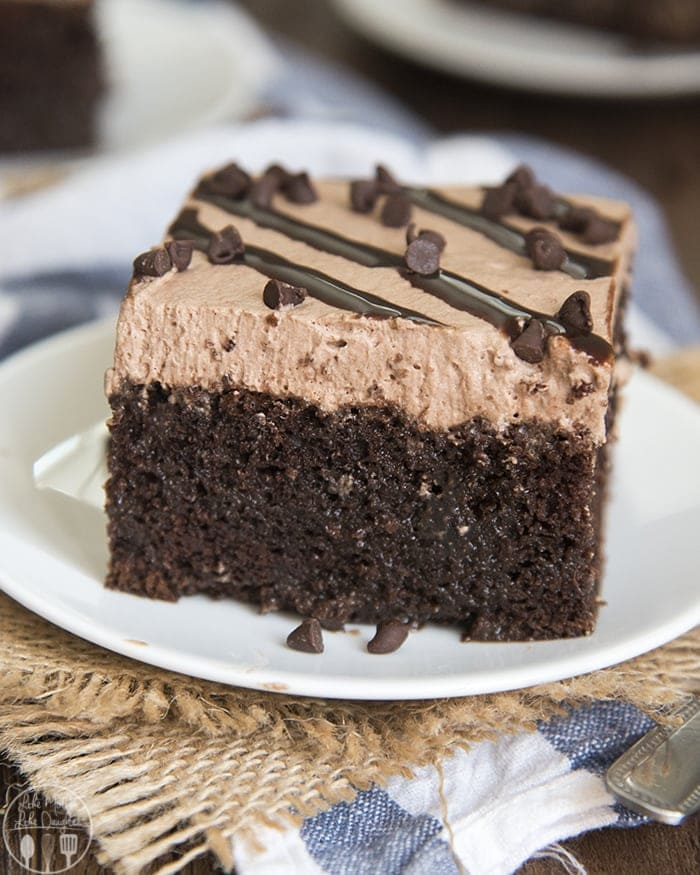 This chocolate poke cake is a rich and decadent chocolate cake that is filled with hot fudge sauce, and topped with chocolate whipped cream!