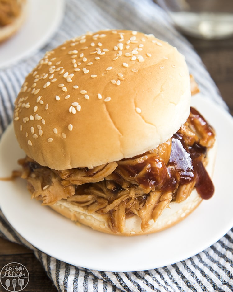 A bbq chicken sandwich on a white plate. The chicken is shredded and bbq sauce is dripping off the side, it is on a sesame bun.