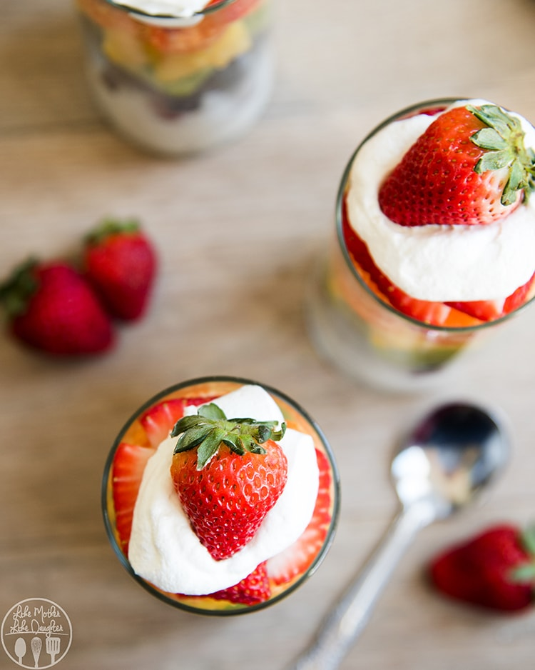 Rainbow Fruit Parfaits topped with cool whip and a strawberry