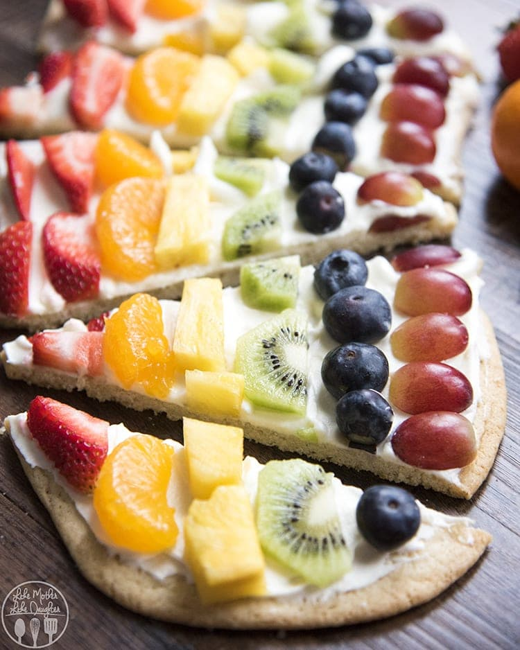 This rainbow fruit pizza is a beautiful fruit pizza topped with the best cream cheese frosting, and decorated with a variety of colored fruits, and made to look like a rainbow!