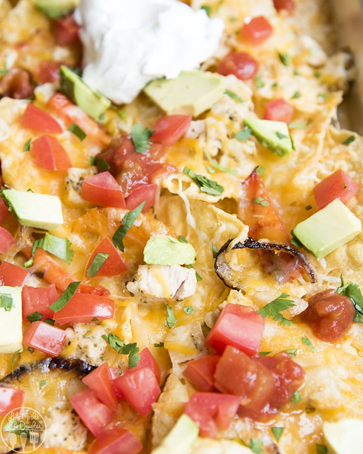 Sheet Pan Nachos topped with chicken, diced tomatoes, salsa, sour cream, avocado, and cilantro.