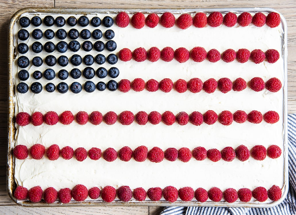 An American flag cake decorated with blueberries and raspberries to make an American flag