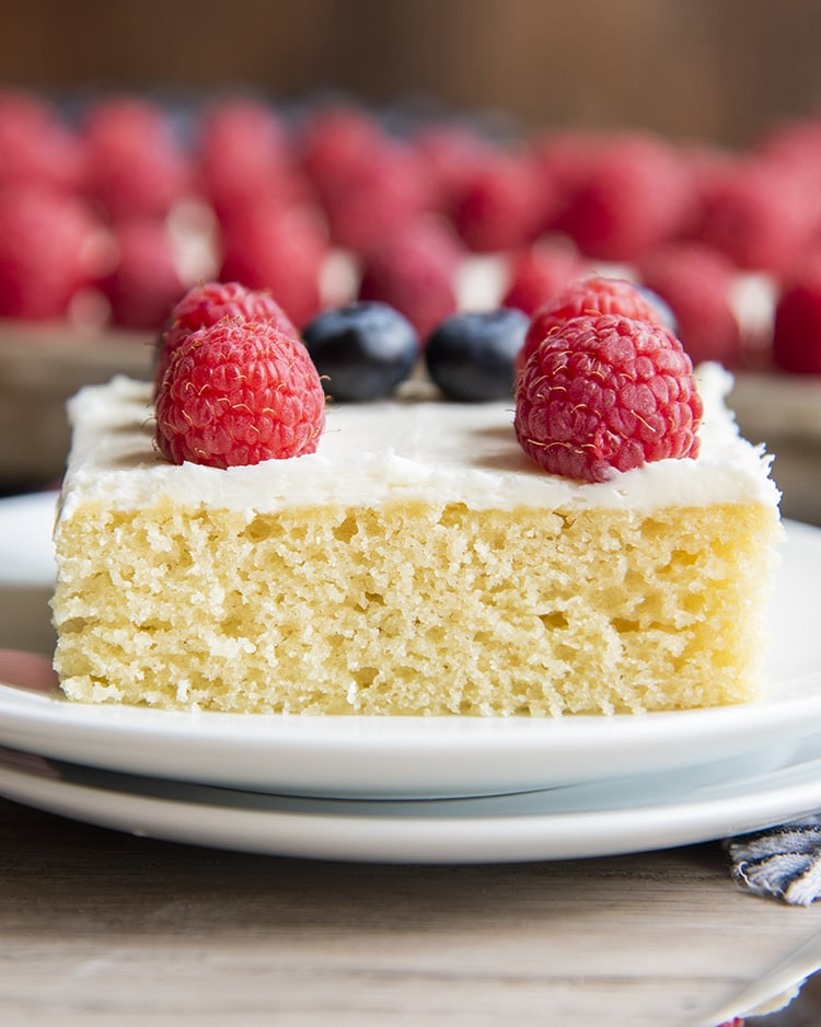 A slice of a white sheet cake with raspberries on top