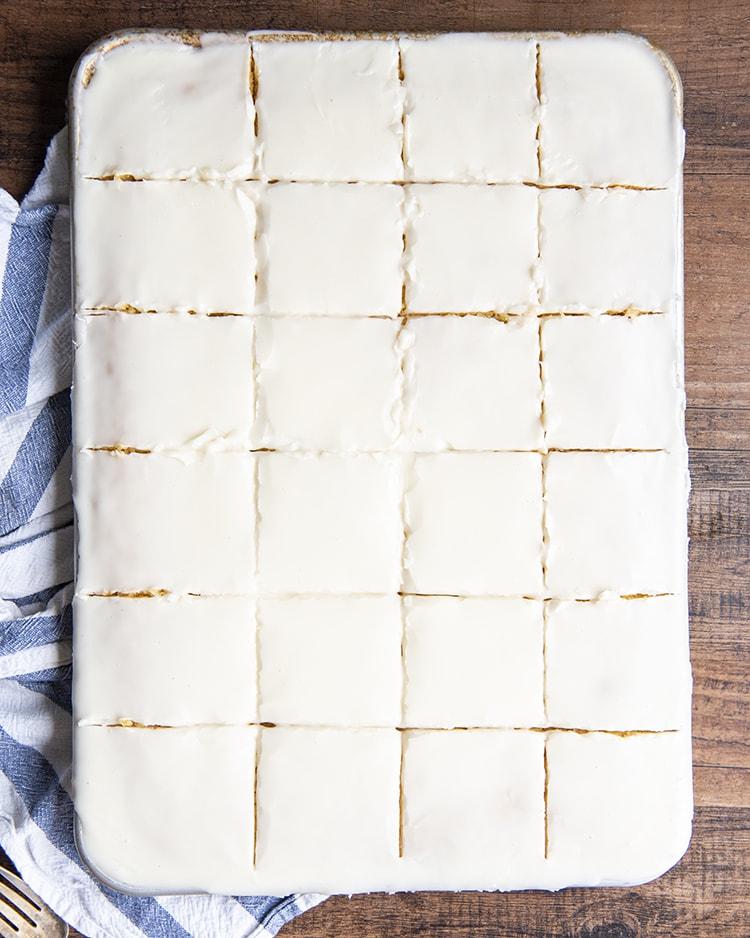 A white sheet cake sliced into twenty four slices