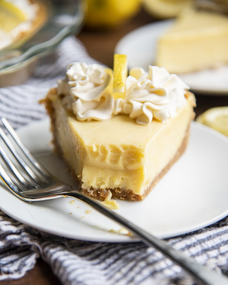 A slice of lemon cream pie with a bite taken out of it