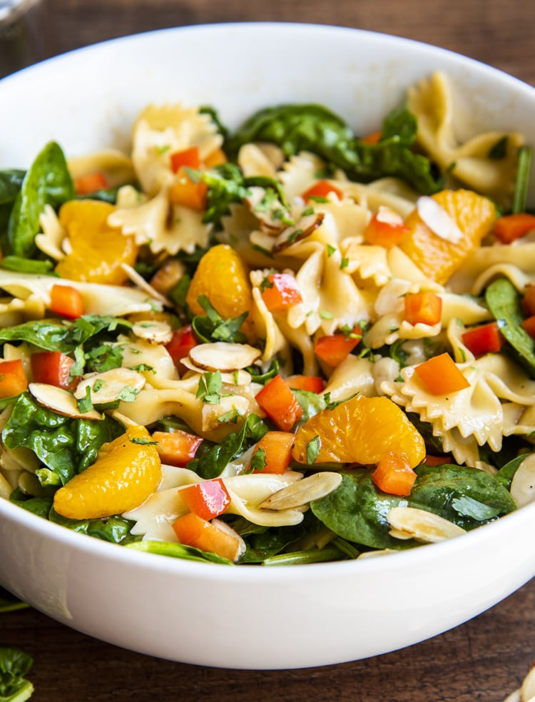 A side shot of a spinach pasta salad with bow tie noodles, mandarin oranges, spinach, cilantro, and bell peppers in a white bowl