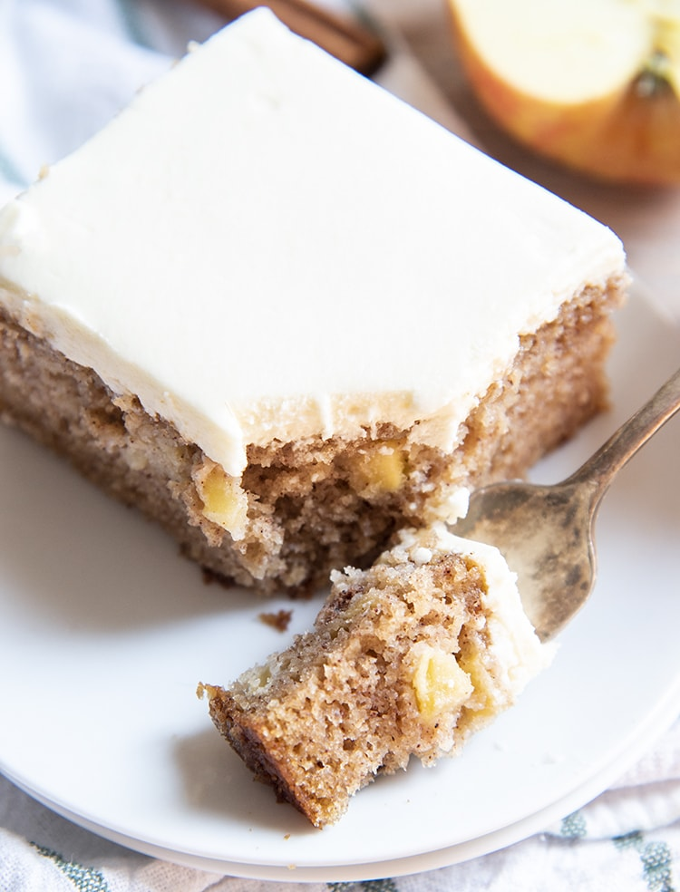 A piece of apple cake with a bite out of it on a plate.