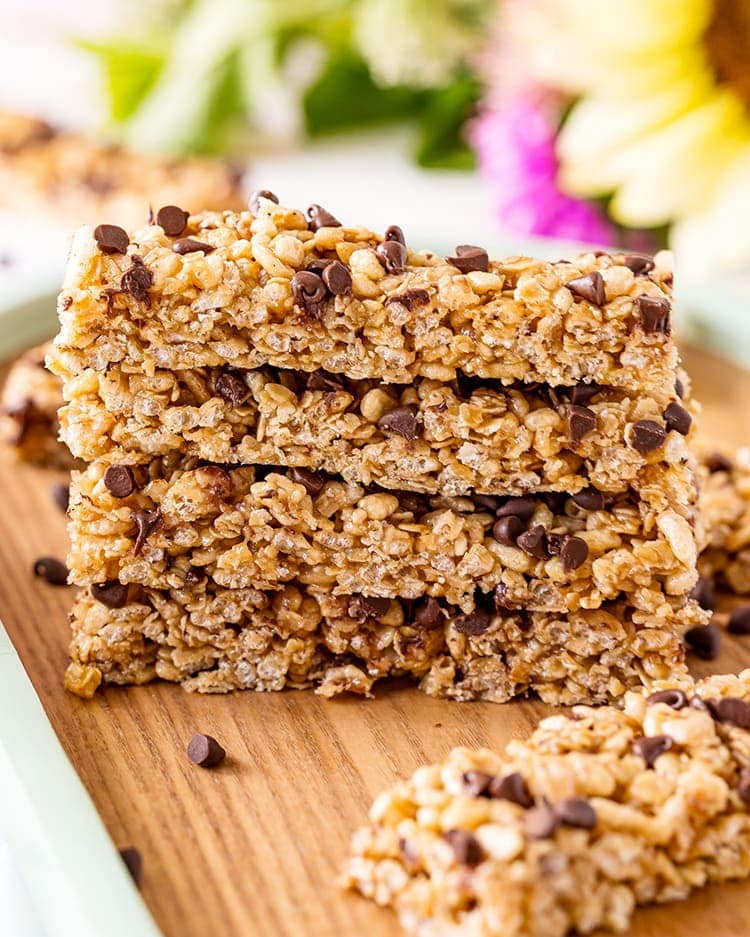 A stack of Peanut Butter Chocolate Chip Granola Bars on a wooden board with flowers in the background