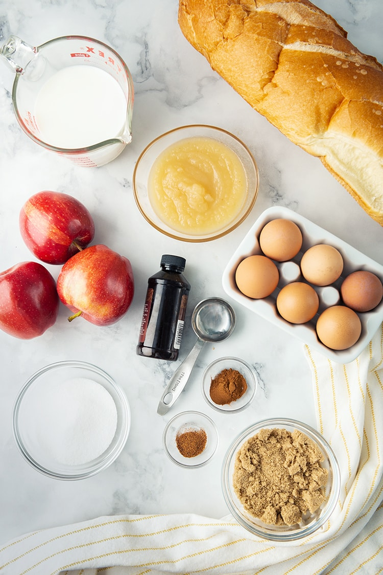 The ingredients needed to make baked apple french toast, apples, eggs, french bread, applesauce and more.