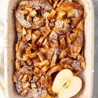 Overnight apple french toast in a pan with a sliced apple