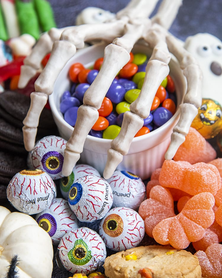 A bowl of orange, green, and purple chocolate candies with a skeleton hand over the top.