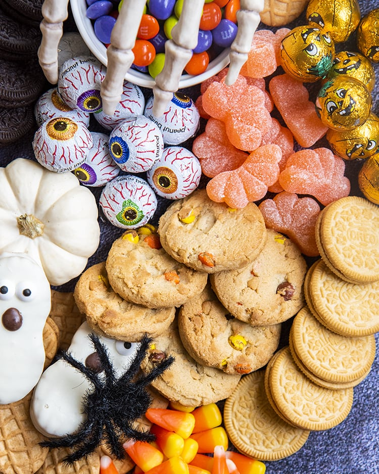 A close up or cookies, and Halloween treats piled together.