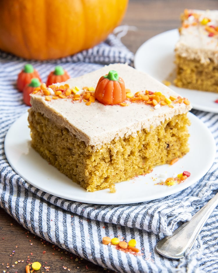 A pumpkin barA pumpkin bar is topped with cinnamon frosting, orange and yellow sprinkles, and a candy pumpkin in the middle.