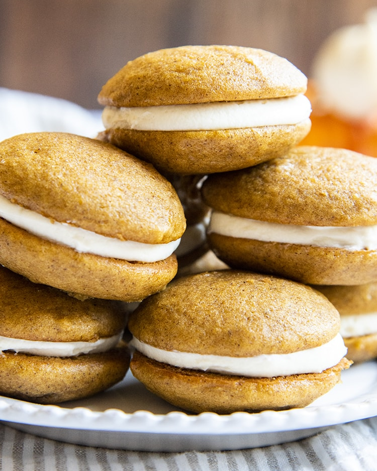A stack of pumpkin whoopie pies on a plate.