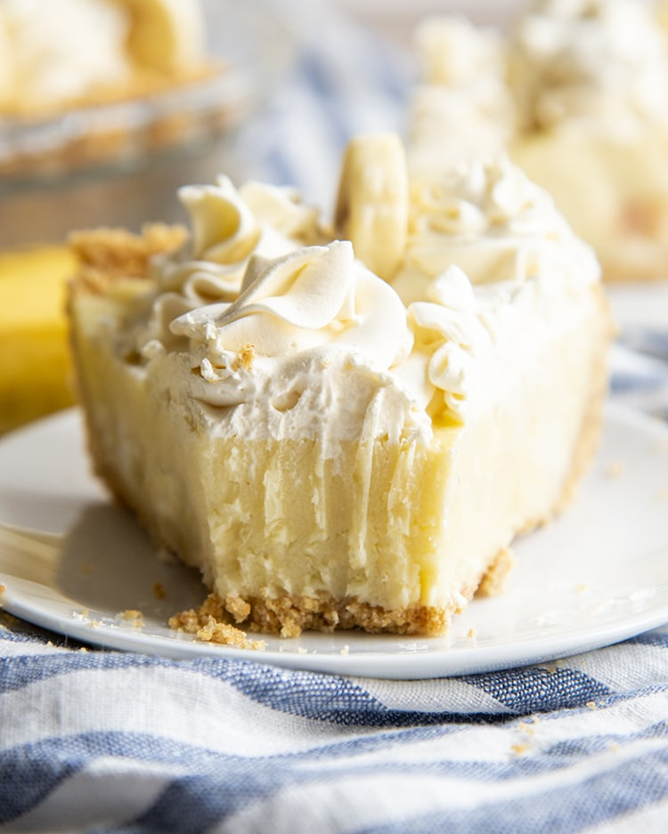 A fork bite taken out of a slice of banana cream pie topped with whipped cream.