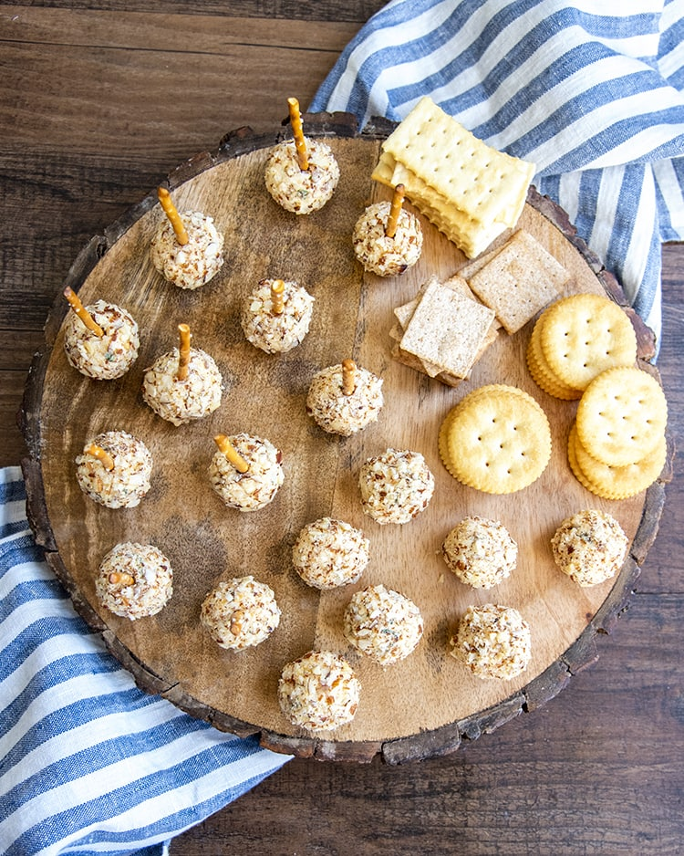 Cheese Ball Bites on a wooden round board with pretzel sticks in half of them, and crackers laid on the side.