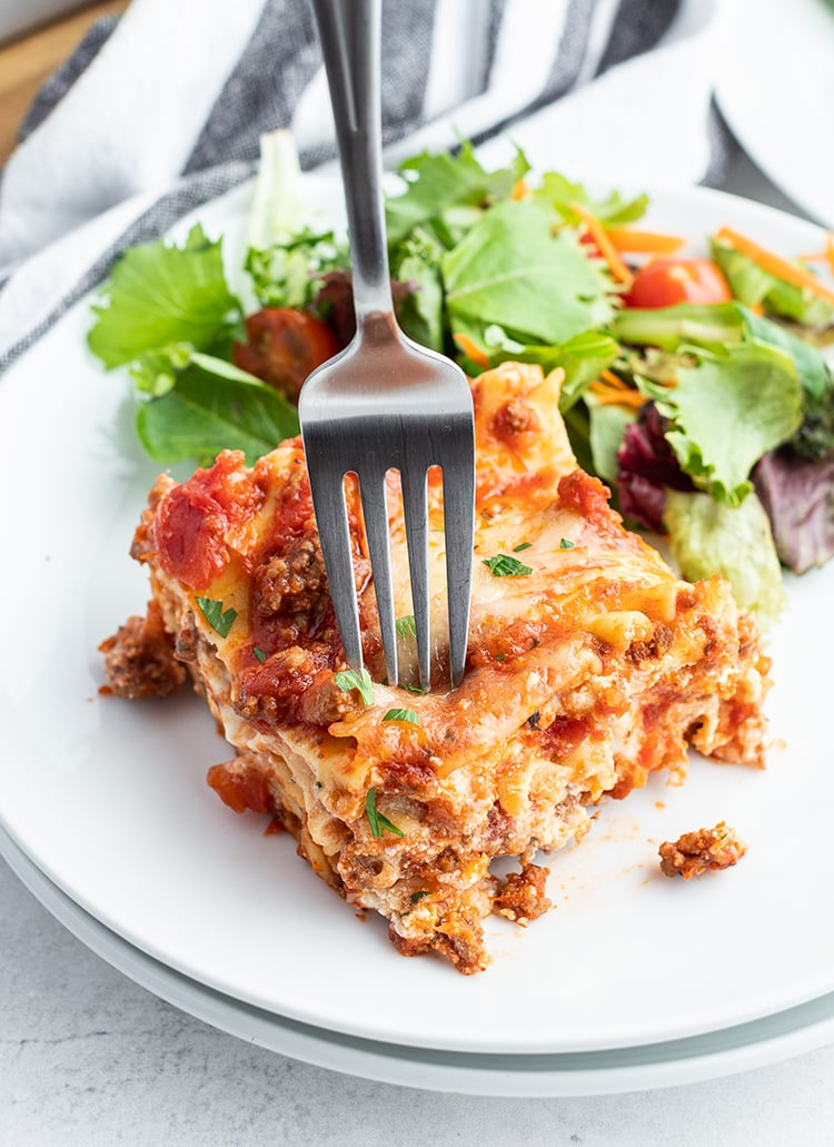 A piece of classic lasagna on a white plate with some salad.
