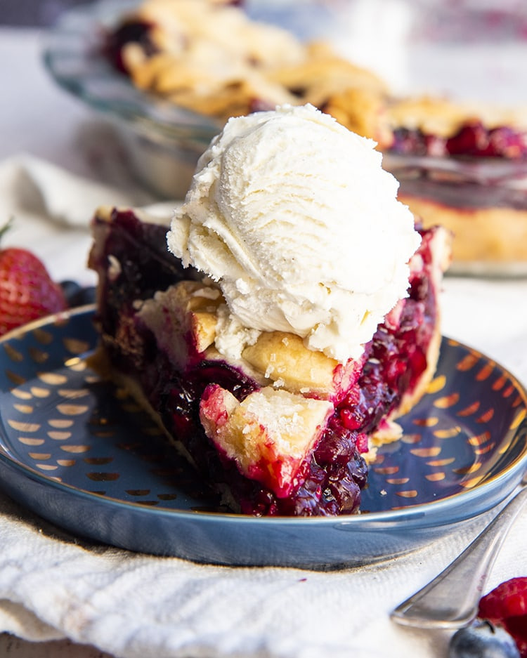 A slice of triple berry pie topped with a scoop of vanilla ice cream!