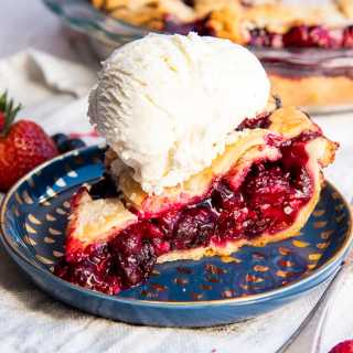 A slice of mixed berry pie on a blue plate showing all the juicy red berries in the middle with a lattice pie crust on top, with a scoop of vanilla ice cream on top.