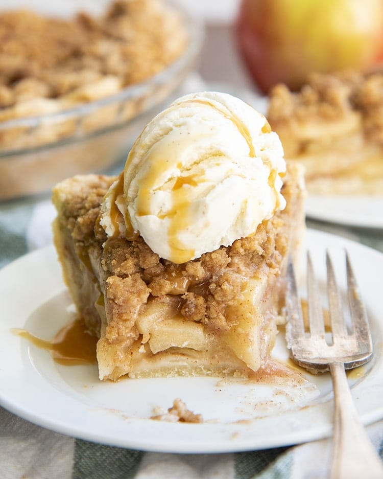 A slice of dutch apple pie with a bite out of it, then topped with ice cream, all on a plate.