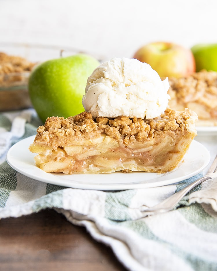 A slice of apple pie on a white plate, topped with vanilla ice cream, with apples behind it.