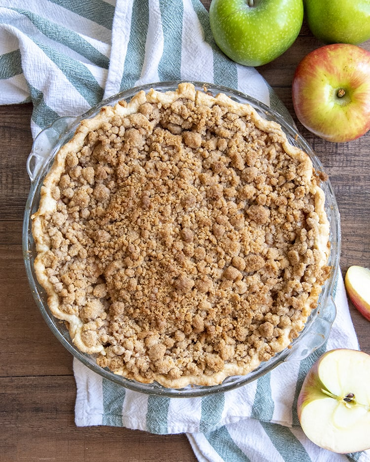 A whole dutch apple pie in a pie pan, showing the streusel crumb on the top. On the side of the pie are some apples.