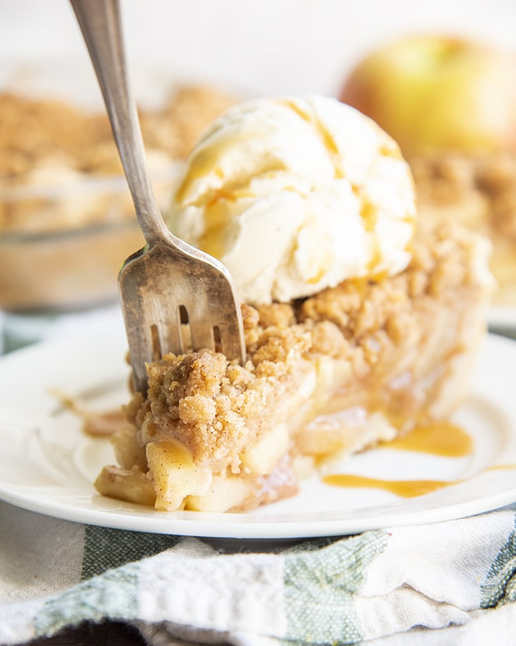 A slice of apple pie topped with a streusel crumb, and a scoop of vanilla ice cream, drizzled with caramel. There is a fork in the front of the pie going to take a bite.