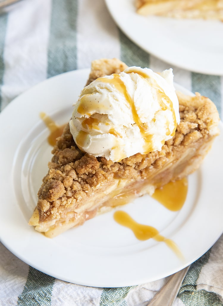A slice of apple pie topped with a streusel crumb, and a scoop of vanilla ice cream, drizzled with caramel.