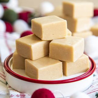 A small plate stacked with a light brown colored peanut butter fudge in a pile.