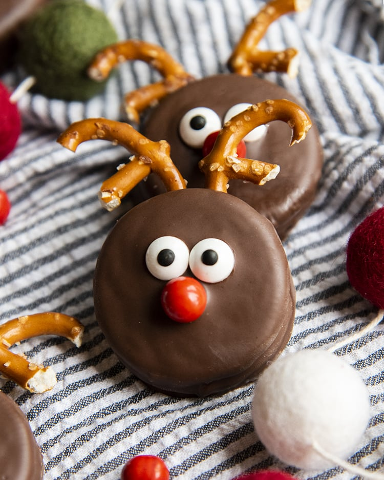 Two Oreo Reindeer on a pinstriped cloth. One is leaning on the other. They are chocolate dipped Oreos decorated to look like reindeer with pretzel antlers, two candy eyes in the middle, and a red candy nose below.
