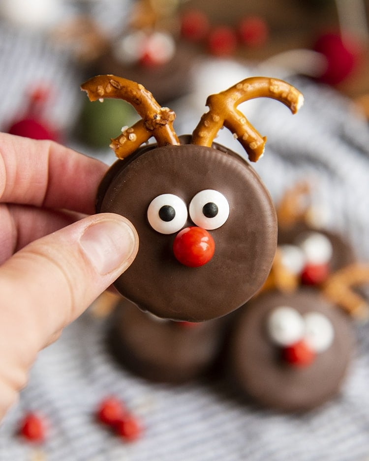 An Oreo dipped in chocolate and decorated to look like a reindeer with pretzel pieces for antlers, candy eye balls and a red sixlet nose. It's being held up by a hand.