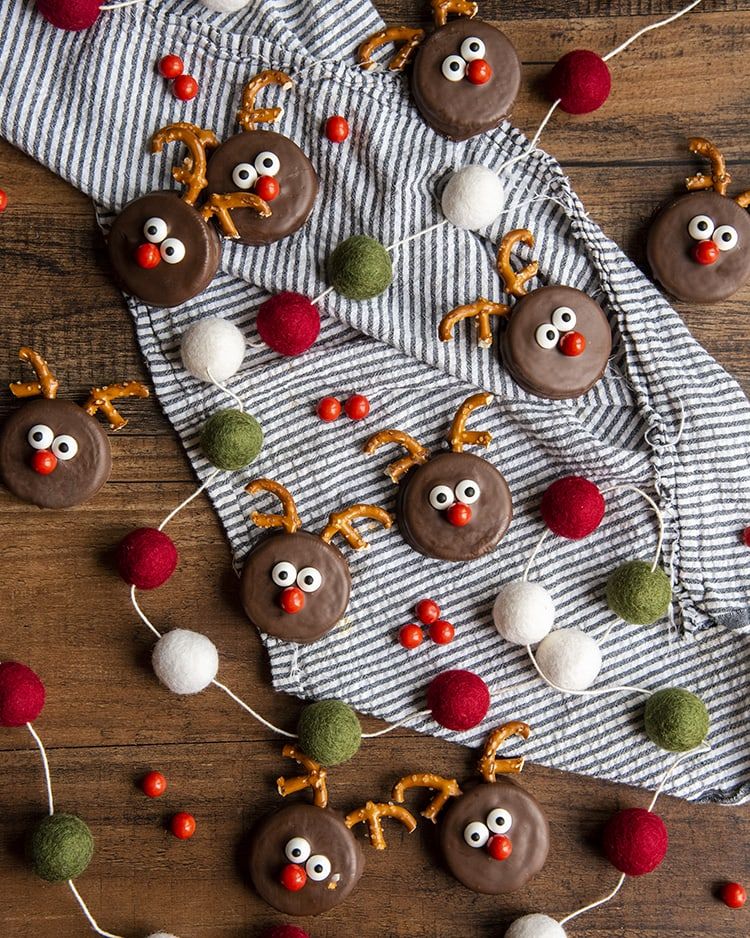 Oreo decorated to look like little reindeer treats, with pretzel antlers, candy eyes, and a red candy nose, arranged out on a cloth with a christmas garland around them.